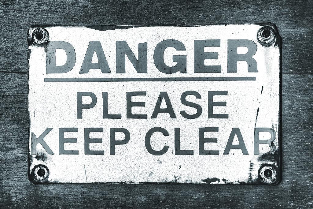 """Il cartello in inglese """"Danger – please keep clear"""" per giocare col doppio senso di """"clear"""": tener libero ed essere chiaro."""