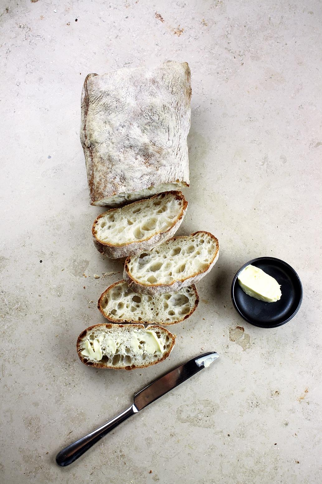 Si vede una ciabatta con burro e coltello come simbolo per il pane quotidiano di Katrin Walter: la lingua tedesca. Foto: Unsplash (Toa Heftiba)