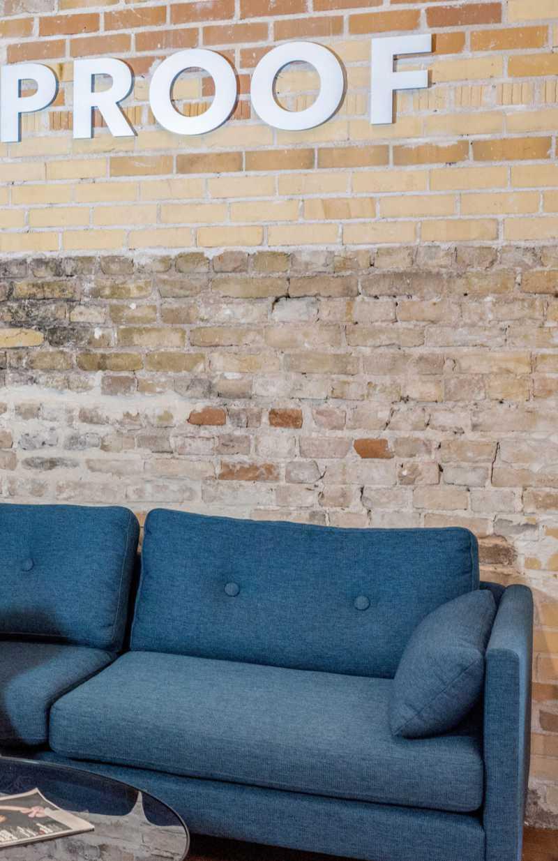 """Divano blu davanti a un muro di mattoni con la scritta """"Proof"""". Ogni tanto vale la pena mettere alla prova la propria comunicazione. Katrin Walter – simply walter"""